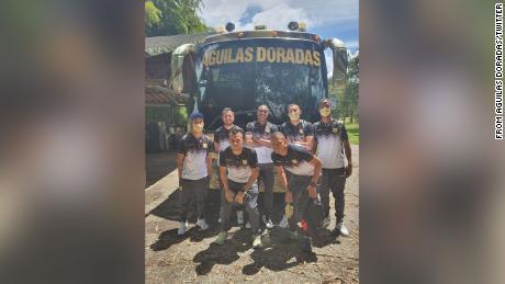 Águilas Doradas' depleted team pose for a photo next to the team bus.