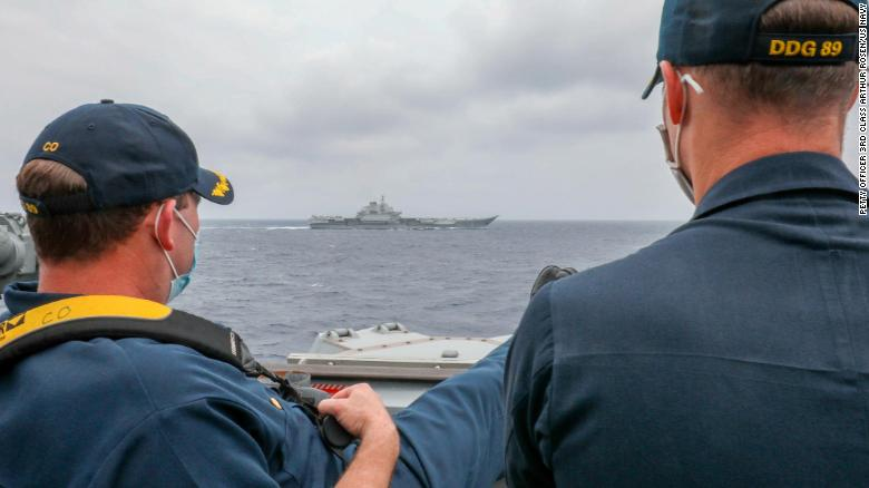 US Navy Cmdr. Robert J. Briggs and Cmdr. Richard D. Slye monitor the Chinese aircraft carrier Liaoning from the pilothouse of the guided-missile destroyer USS Mustin on April 4 in the Philippine Sea.
