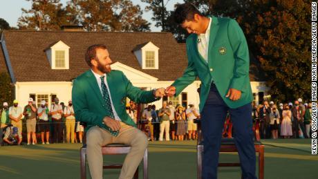 Matsuyama fist bumps 2020 champion Dustin Johnson during the Green Jacket ceremony after Matsuyama won the Masters.