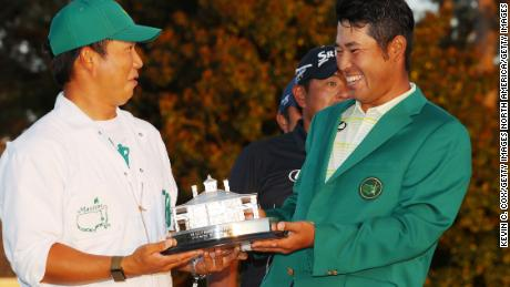 Matsuyama poses with his caddy, Hayafuji and the Masters Trophy.