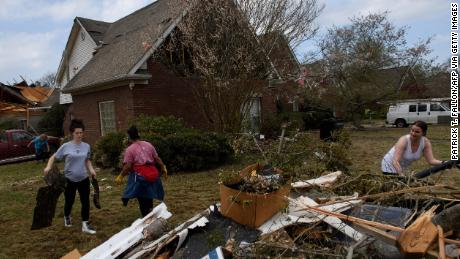 Volunteers clean up debris on March 26, following a tornado that hit the Eagle Point community south of Birmingham, Alabama.