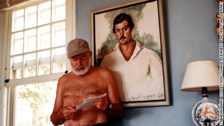 Ernest Hemingway at his home in Cuba, circa 1953, standing in front of a 1929 portrait of himself by Waldo Pierce.