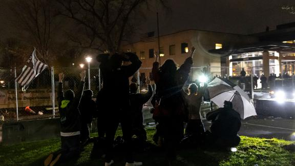 """Demonstrators shout """"Don't shoot"""" at the police after curfew as they protest the death of Daunte Wright who was shot and killed by a police officer in Brooklyn Center, Minnesota on April 12, 2021. - A suburb of Minneapolis was under curfew early April 12, 2021 after US police fatally shot a young Black man, sparking protests not far from where a former police officer was on trial for the murder of George Floyd.Hundreds of people gathered outside the police station in Brooklyn Center, northwest of Minneapolis, with police later firing teargas and flash bangs to disperse the crowd, according to an AFP videojournalist. (Photo by Kerem Yucel / AFP) (Photo by KEREM YUCEL/AFP via Getty Images)"""