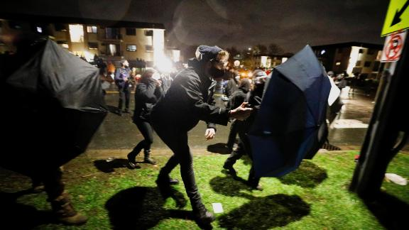 Some protesters advance toward officers Monday using umbrellas as shields.