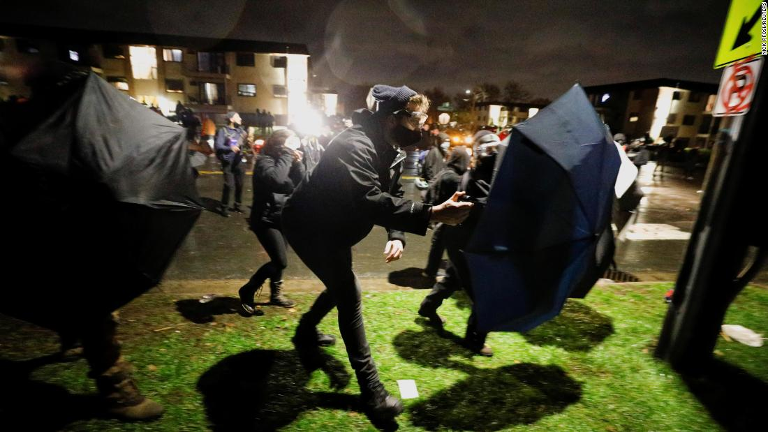 Protesters advance toward officers using umbrellas as shields.