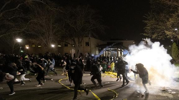 People run as police try to disperse a crowd at the Brooklyn Center Police Department on Sunday.