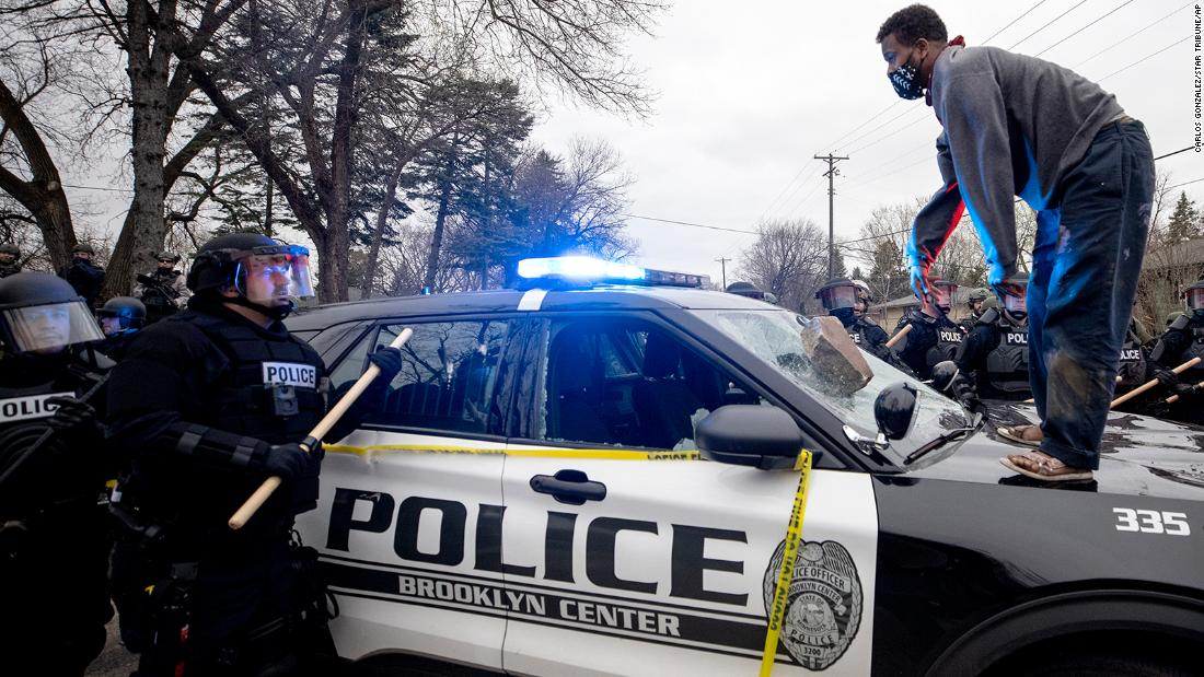 A man stands atop a police car after throwing a brick at the windshield on April 11.