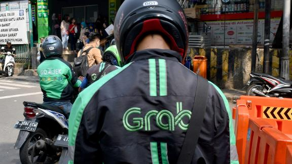 "GrabBike riders wait for passengers outside a commuter train station in Jakarta on June 13, 2018. - Toyota said June 13 it was investing 1 billion USD in Asia ride-share company Grab, as the Japanese automaker looks to expand beyond its core business into the ""mobility"" sector. (Photo by GOH CHAI HIN / AFP)        (Photo credit should read GOH CHAI HIN/AFP via Getty Images)"