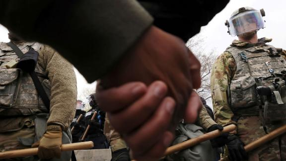Members of the National Guard watch as protesters hold hands during a rally outside the Brooklyn Center Police Department on Monday.