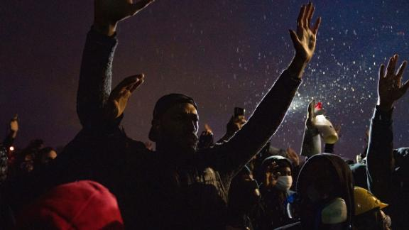 Protesters raise their hands in front of the Brooklyn Center Police Department on Monday.