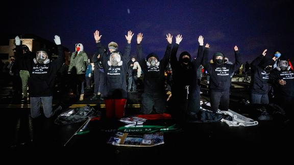 Activists raise their arms as they confront State troopers, National Guard members, and other law enforcement officers on Tuesday.