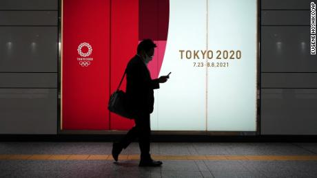 A man wearing a protective mask to help curb the spread of coronavirus goes near advertising for the 2020 Olympics in Tokyo at a downfall on Tuesday, April 6 in Tokyo.