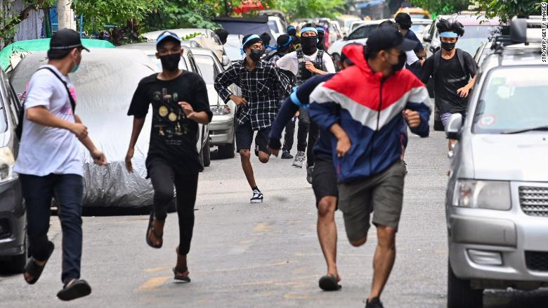 Protesters run from security forces during an ant-coup demonstration in Yangon, Myanmar, on Monday, April 12.