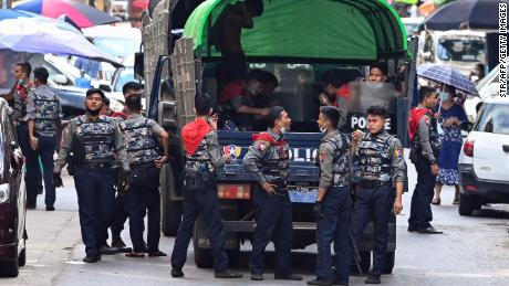 Police talk as they arrive at the site of a demonstration by protesters against the military coup in Yangon on April 12, 2021. (Photo by STR / AFP) (Photo by STR/AFP via Getty Images)