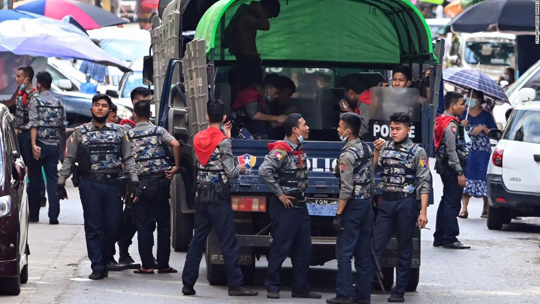 Police talk as they arrive at the site of a demonstration in Yangon on April 12.