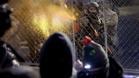A police officer pepper-sprays demonstrators on Tuesday.