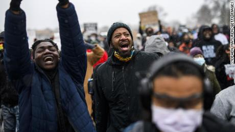 Minnesota State Rep. John Thompson, center, marches with protesters outside the Brooklyn Center police headquarters on Tuesday in Brooklyn Center, Minnesota.