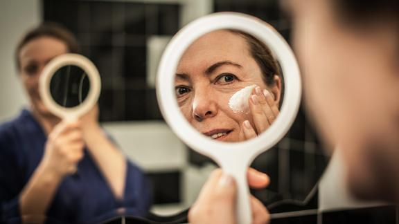 Woman applying face cream in mirror