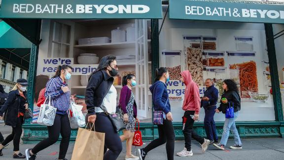 People wearing face masks walk past the Bed Bath & Beyond store. Bed Bath & Beyond has announced plans to permanently close about 200 stores over the next two years. This announcement appears to be the first iteration of that plan, report says.