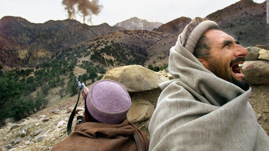 An Afghan Northern Alliance fighter bursts into laughter as US planes strike a Taliban position near Tora Bora, Afghanistan, in December 2001. Afghan militia leaders declared victory in the battle of Tora Bora and claimed to have captured al Qaeda's last base.