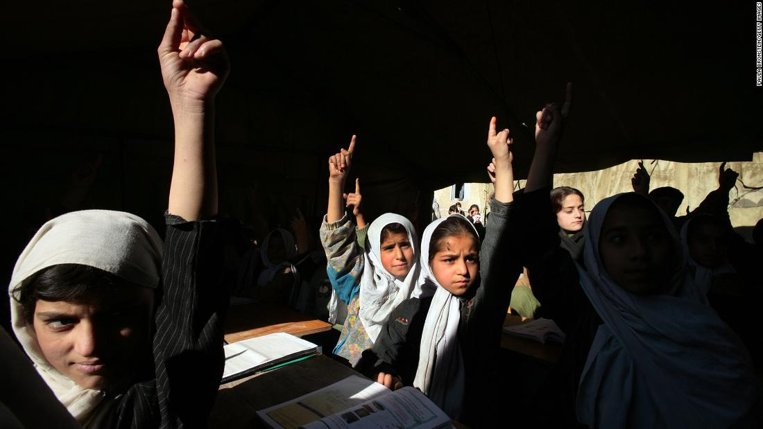 "Girls at the Bibi Mahroo High School raise their hands during an English class in Kabul in November 2006. After the fall of the Taliban, millions of Afghan girls <a href=""https://www.cnn.com/2012/09/26/world/asia/cnnheroes-afghan-schoolgirls"" target=""_blank"">were able to attend school</a> and get the education that their mothers couldn't."