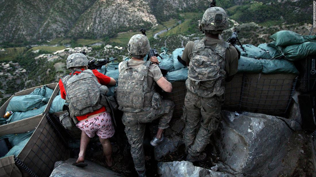 "US soldiers take defensive positions after receiving fire from Taliban positions in Afghanistan's Korengal Valley in May 2009. Army Spc. Zachary Boyd was still in his ""I love NY"" boxers because he rushed from his sleeping quarters to join his fellow platoon members."
