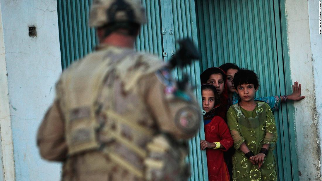 Children watch a Canadian soldier conducting a dusk patrol in Kandahar, Afghanistan, in October 2009.