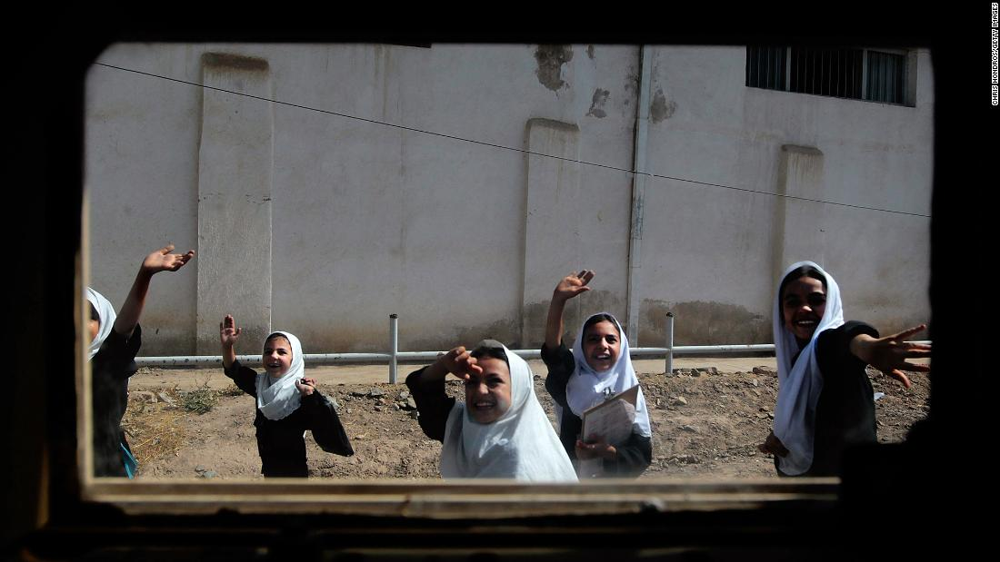 Schoolgirls are seen through the window of a Humvee as they wave to a passing American convoy in Herat, Afghanistan, in June 2010.