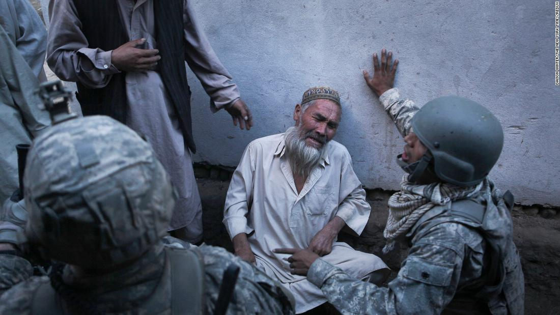 A man cries while talking to US soldiers in Naghma Bazaar, Afghanistan, in September 2010. The man said Taliban fighters had forced their way into his home and demanded food and milk before getting into a firefight with American soldiers.