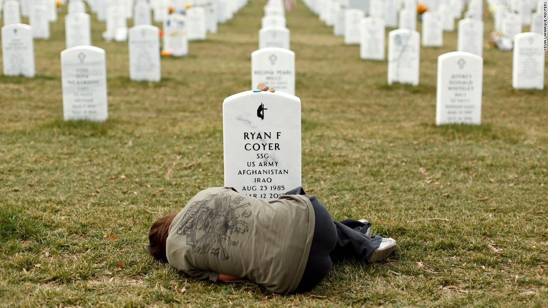Lesleigh Coyer lies down in front of the grave of her brother, Army Staff Sgt. Ryan Coyer, at Virginia's Arlington National Cemetery in March 2013. He died of complications from an injury sustained in Afghanistan.