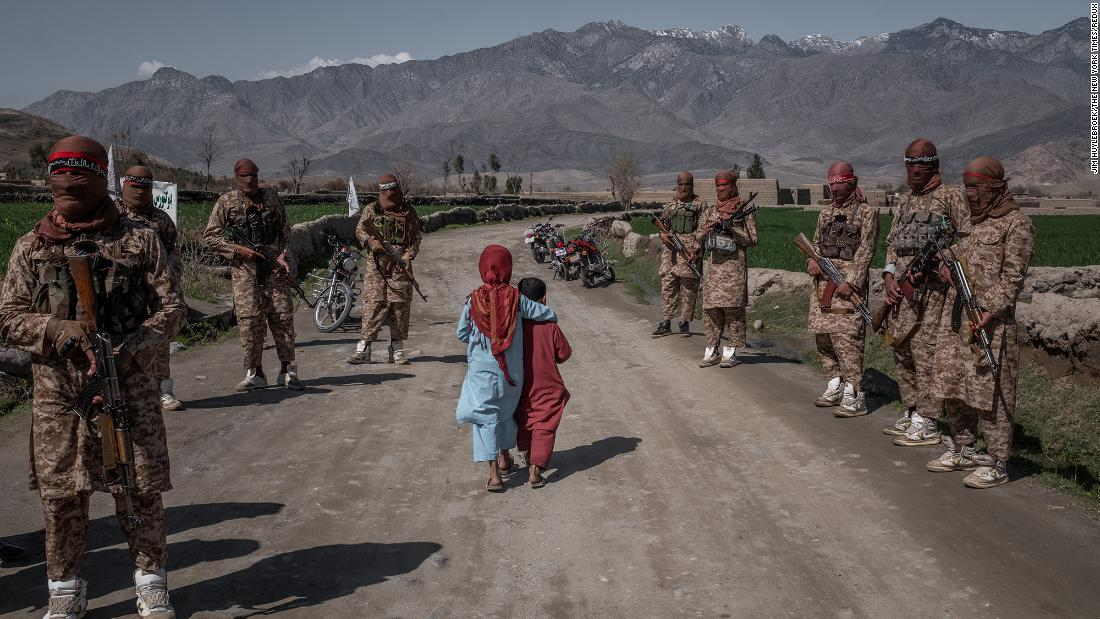 "Two children pass members of a Taliban Red Unit in Afghanistan's Laghman province in March 2020. A month earlier, the United States and the Taliban <a href=""https://www.cnn.com/2020/02/29/politics/us-taliban-deal-signing/index.html"" target=""_blank"">signed a historic agreement.</a>"