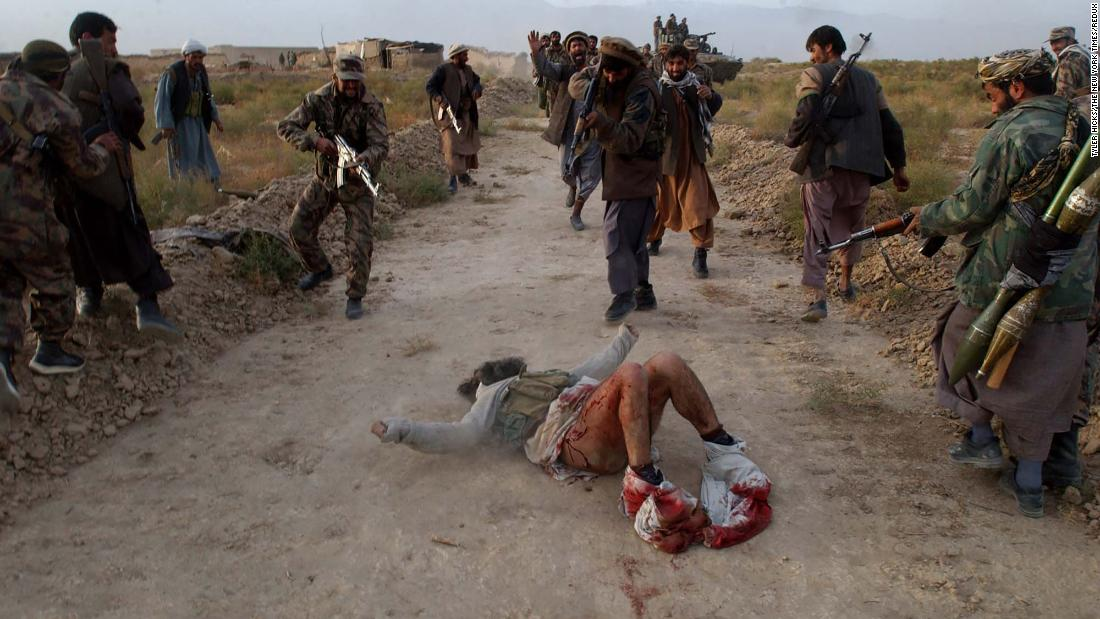 Members of the Afghan Northern Alliance, an anti-Taliban group, kill a wounded Taliban fighter they found while advancing toward Kabul, Afghanistan, in November 2001. US airstrikes and Northern Alliance ground attacks led to the fall of Kabul that month.