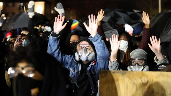 Demonstrators hold their hands up as they protest outside of the Brooklyn Center Police Department on Wednesday.