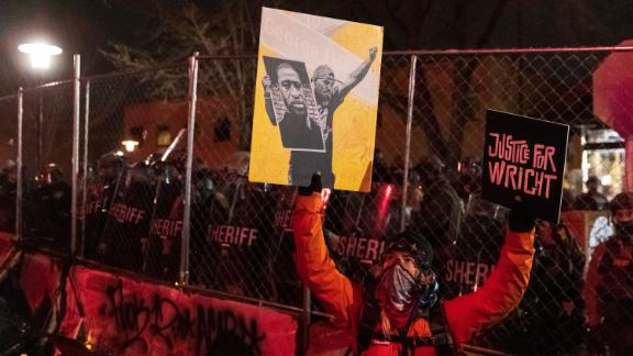 """A demonstrator holding a poster of George Floyd and sign reading """"Justice for Wright"""" in front of a line of police officers outside the Brooklyn Center police building."""