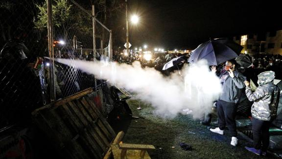 Pepper spray is used from behind the fenced perimeter of the Brooklyn Center Police Department on Wednesday.