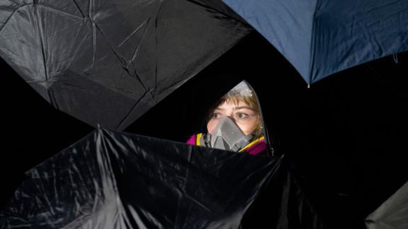 A demonstrator is seen behind umbrellas.