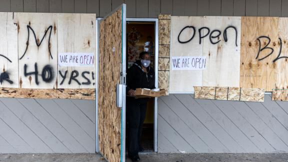 A customer steps out of a store Wednesday that was boarded up as a result of the previous night's unrest.