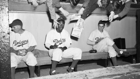 Young Dodger fans reach down to try to get Robinson's autograph during an exhibition game in New York on April 11, 1947.