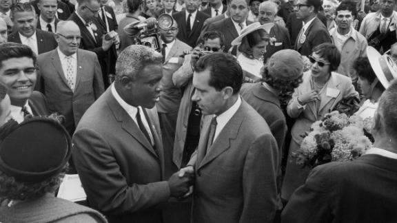 Robinson shakes hands with President Richard Nixon at a GOP rally in 1960. Robinson attended the 1964 Republican Convention, but he later supported Democrats as the political parties' makeup changed.
