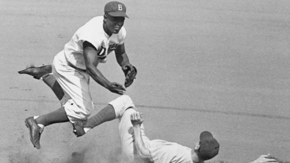 Robinson leaps into the air to try to turn a double play in 1952.