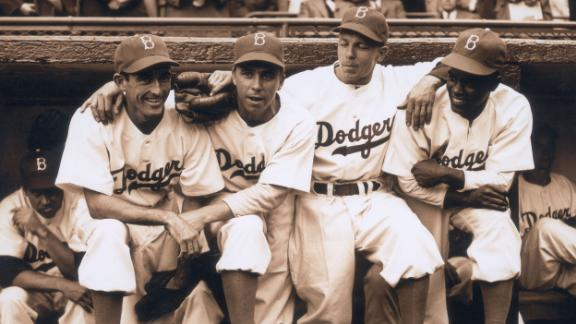"""Robinson poses in the dugout with Dodgers teammates as he makes his historic debut on April 15, 1947. With Robinson, from left, are Johnny """"Spider"""" Jorgensen, Harold """"Pee Wee"""" Reese and Eddie Stanky."""