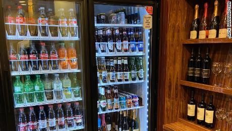 A fridge full of Coke beverages right near Trump wine bottles at Trump's Las Vegas hotel souvenir shop.