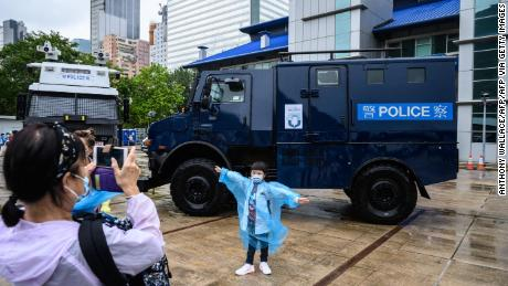 A young visitor poses in front of a police vehicle at the city's police college during an open day to celebrate the National Security Education Day in Hong Kong on April 15, 2021.