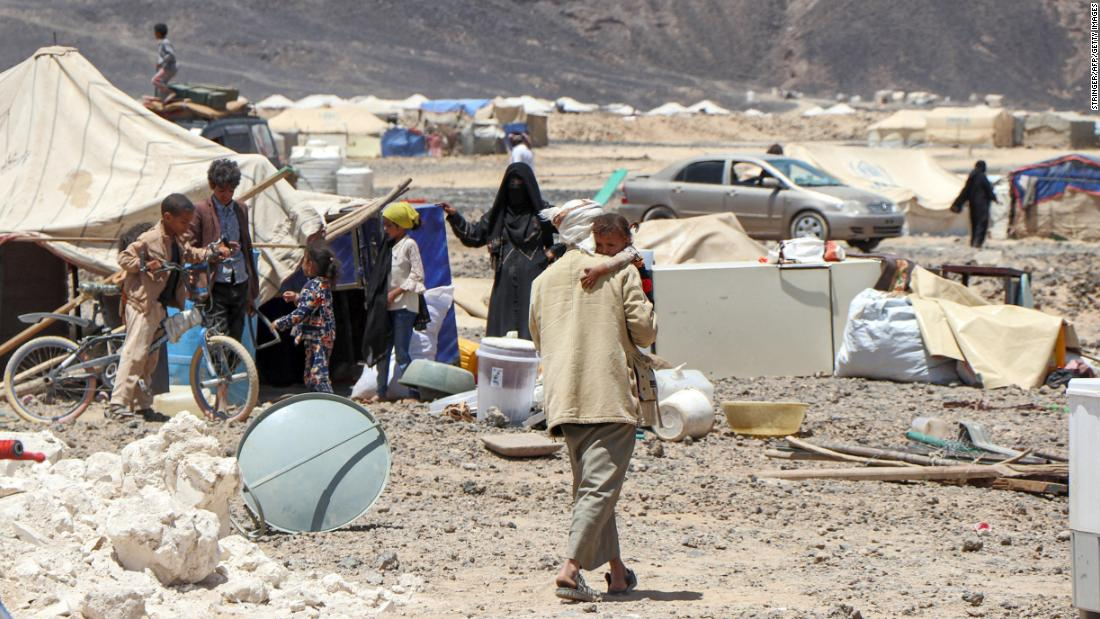 A man carries a child at a camp for displaced people on Marib's outskirts on March 28. Residents were preparing to flee due to the camp's proximity to the fighting.