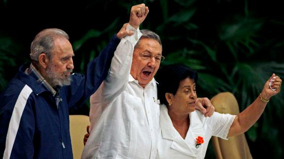 Fidel Castro raises his brother's hand as they sing the International Socialist Anthem during the 6th Communist Party Congress in Havana in 2011.