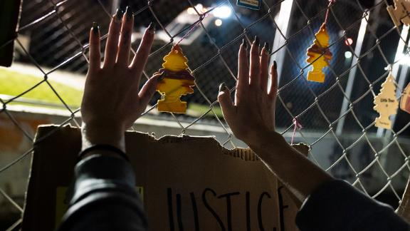 """A demonstrator presses their hands against a perimeter security fence outside the Brooklyn Center Police Department. The fence is adorned with car air fresheners symbolic to the shooting death of Daunte Wright. Moments before police fatally shot Wright during a traffic stop Sunday, he called his mother and <a href=""""https://www.cnn.com/2021/04/12/us/police-shooting-air-freshener-trnd/index.html"""" target=""""_blank"""">told her he'd been pulled over for hanging air fresheners from his rearview mirror.</a> Minnesota is one of at least several states with laws that prohibit hanging items from a vehicle's rearview mirror or affixing them to the windshield on the grounds that they could obstruct the driver's vision. Brooklyn Center Police Chief Tim Gannon told reporters that Wright was originally pulled over for an expired tag and that when officers approached his car, they saw an item hanging from the rearview mirror. Officers ran Wright's name and found a gross misdemeanor warrant, Gannon said."""