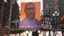 A picture of George Floyd hangs on a fence barrier that surrounds the Hennepin County Government Center on March 30, 2021 in Minneapolis, Minnesota.