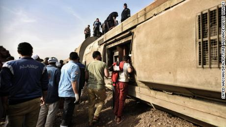 People inspect the damaged wagons of a passenger train that departed on a track near Toukh.
