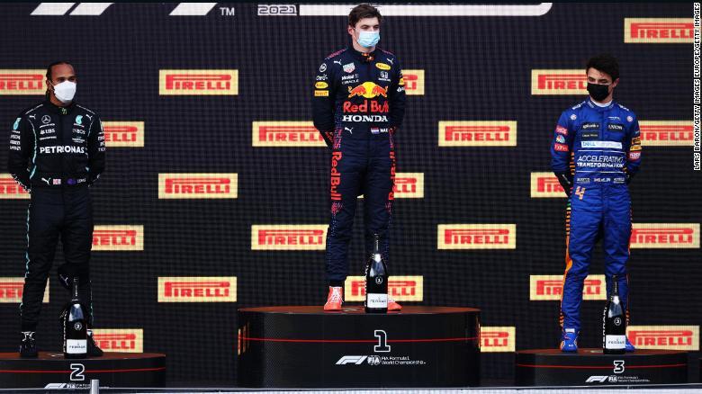 Lewis Hamilton, Max Verstappen dan Lando Norris berdiri di podium.