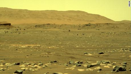 A view from the Perseverance rover shows Ingenuity with its blades in motion.